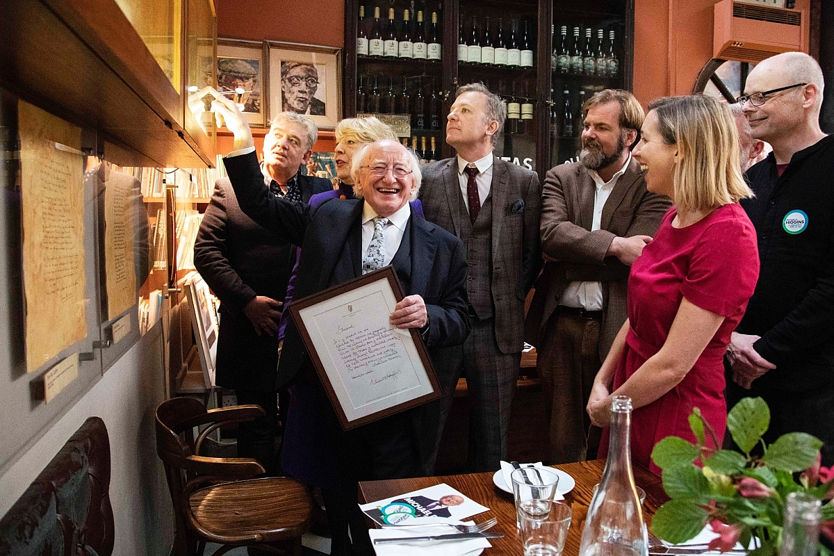 President Michael D Higgins adds his composition Stardust to the Farmgate Poetry wall in October 2018